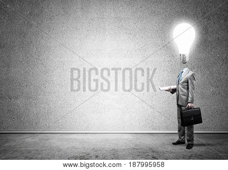 Faceless businessman with glowing light bulb instead of head