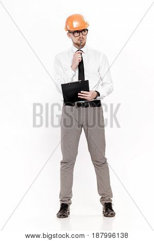 Young construction engineer in orange helmet with a folder thinking on a white background