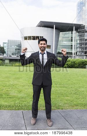 Arabic successful happy smiling cheerful businessman or worker in black suit with tie and shirt with beard standing in front of an office building with raised hands on green grass in summer day.