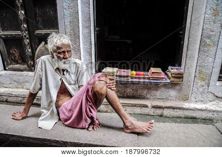 Varanasi India september 19 2010: Old indian man sitting on a flor and selling his books.