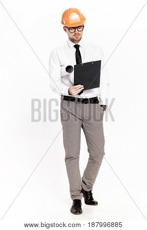 Young construction engineer in orange helmet with a folder on a white background