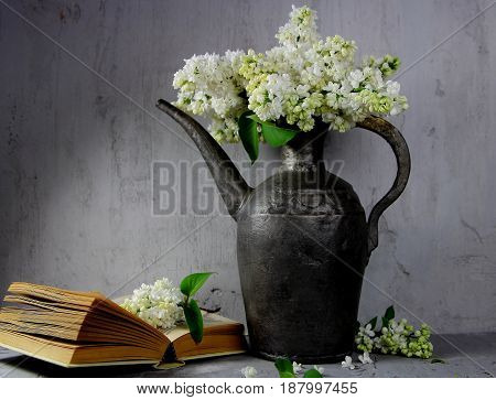 white lilac in a silver pitcher with an open book on the table