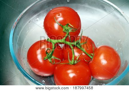 Ripe fresh bunch of red tomatoes in a glass container