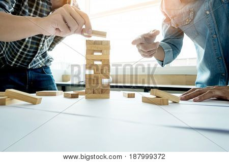 Hand Of Engineer Playing A Blocks Wood Tower Game (jenga) On Blueprint Or Architectural Project.