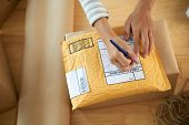 Hands of woman writing address on first class mail package poster