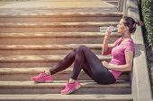 Fitness runner woman drinking water and sitting on staircase. Athlete girl taking a break during run to hydrate during hot summer day. Healthy active lifestyle. poster