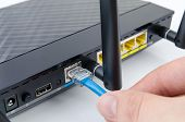 Man plugs internet cable into the router. router wifi ethernet connection network port wireless closeup concept poster