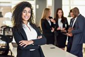 Businesswoman leader looking at camera in modern office with businesspeople working at the background. Teamwork concept. Muslim woman. poster