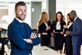 Caucasian businessman leader looking at camera in modern office with multi-ethnic businesspeople working at the background. Teamwork concept. Young man with beard wearing blue suit. poster