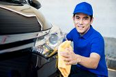 Young man polishing (cleaning) car with microfiber cloth - car detailing valeting and auto service concepts poster