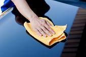 Hand with microfiber cloth polishing car bonnet poster