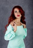 Portrait of beautiful redhead young woman with big boobs in a turquoise dress on a gray background. poster