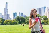 Happy Asian woman texting sms on mobile phone in New york City, NYC. Young girl walking in Central Park meadow in Manhattan. poster