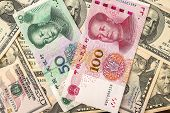 Chinese yuan bank note on USA dollars background, Chinese and USA economy finance trade business, money closeup poster