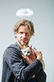 cat and man or handsome macho with white angel halo on head blond hair hairstyle holding cute kitten pet domestic animal in arms on grey background. Friendship and care. Good and evil poster