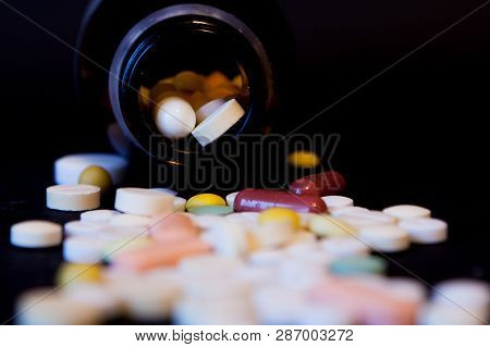 A Bottle Of Spilled Pills On Black Background.levitating Tablets. Tablets On A Dark Background That