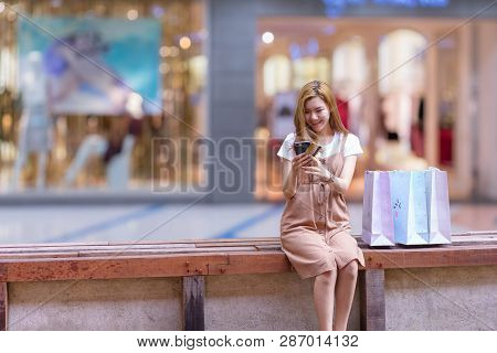 Asian Woman Shopping Holding Shopping Bag And Use Of Mobile Phone And Credit Or Debit Card At Shoppi