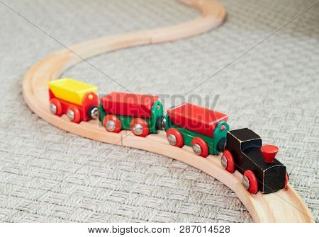 Wooden Toy Train Running On Miniature Railroad. The Black Engine Pulling Colorful Cars On The Floor.