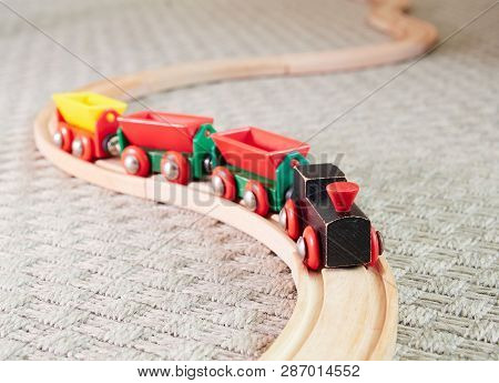 Wooden Toy Train Running On Miniature Tracks. The Black Engine Pulling Colorful Cars On The Floor. E