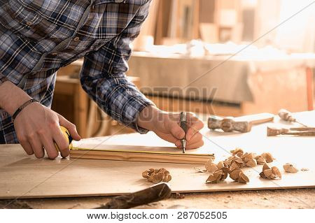 Carpenter Working With Meter Or Rule Taking Measures On Wood Using Pencil. Workshop Background. Carp