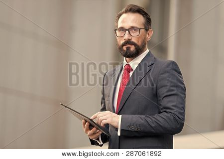 Businessman With Tablet In Hand On Office Building Background. Businessman Using His Tablet Out Of O