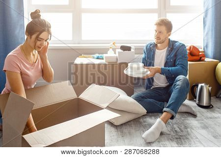 Young Family Couple Bought Or Rented Their First Small Apartment. Guy Sit On Floor And Hold White Pl