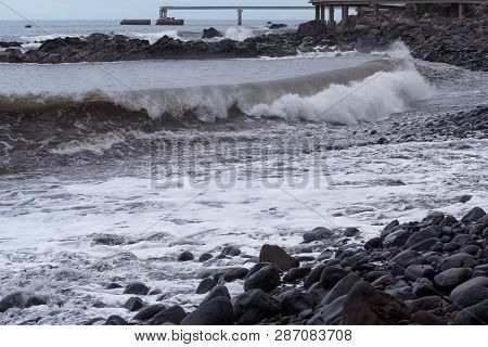 Big Wave Breaking On A Stone Coastline At Stormy Weather. Portuguese Island Of Madeira