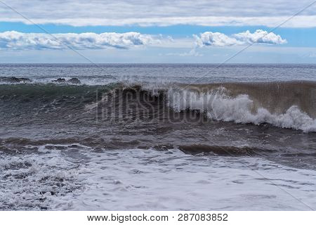 Frontal View At Winding Wave Against Cloudy Blue Sky. Portuguese Island Of Madeira