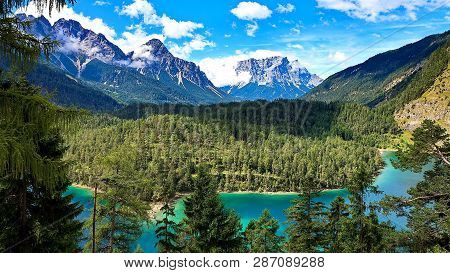River On The Background Of Snowy Mountains And Taiga. Taiga On The Mountain Slopes. Mountain Landsca