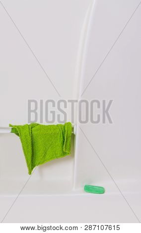 Vertical close-up shot of the wall of a white bathtub.  Green washcloth hanging from handrail and green bar of soap on shelf.  Lots of copy space. poster