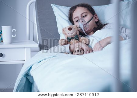 Sad Kid With Cystic Fibrosis Lying In A Hospital Bed With Oxygen Mask And Plush Toy
