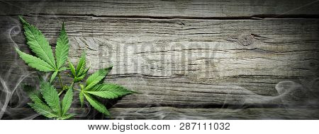 Cannabis Sativa Leaves With Smoke On Wooden Table - Medical Legal Marijuana