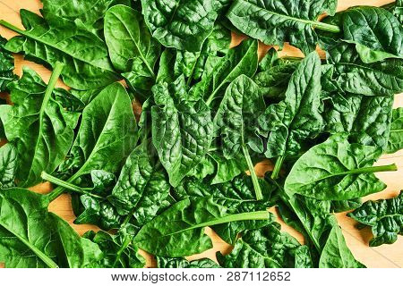 Fresh Spinach Leaves Unwashed On Wooden Table. Spinach Background. Top View With Copy Space For Text