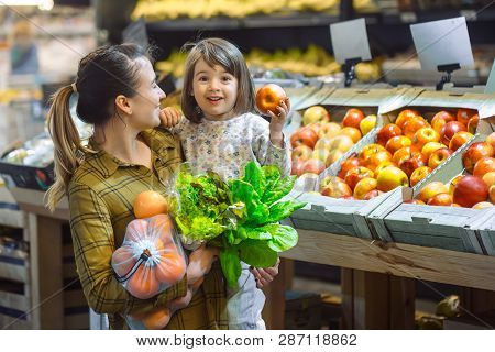 Family In The Supermarket. Beautiful Young Mom And Her Little Daughter Smiling And Buying Food. The