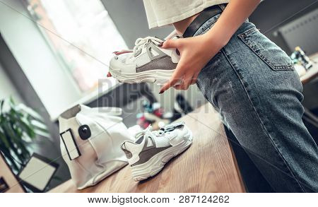 Close-up Of Woman In Shoe Shop Chooses Sneakers. Shopping In Boutique Of Fashionable Shoes. A Young