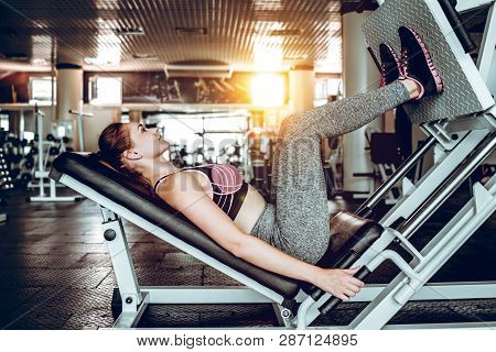 Workout With Simulator Leg Press At Gym.woman Is Engaged In Fitness At Gym.