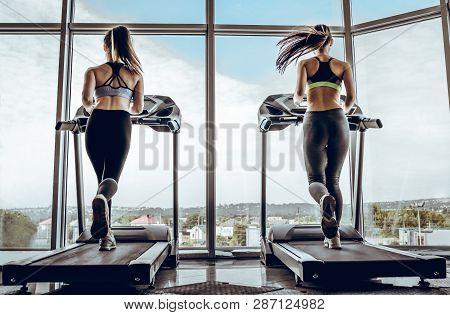 Back View Of Sports People On Running Track. Two Attractive Young Women Are Running In Gym. Treadmil