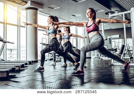 Sportive Young Women In A Gym Training. Working Out In A Fitness Gym. Side View.