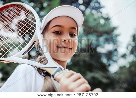 Tennis Training For Young Kid Outdoors. Portrait Of Happy Sporty Little Girl On Tennis Court. Caucas