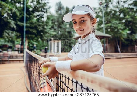 Child Playing Tennis On Outdoor Court. Little Girl With Tennis Racket And Ball In Sport Club. Active