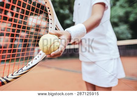 Sporty Little Girl Preparing To Serve Tennis Ball. Close Up View Of Beautiful Yong Girl Holding Tenn