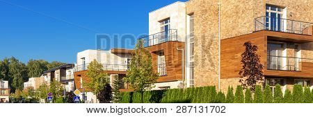 Townhouses In Town Or Village. Panoramic Scenic View Of The Modern Houses In Summer. Street With Con
