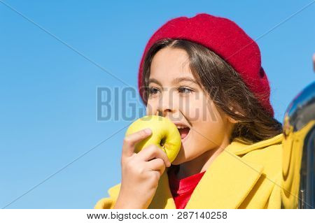 Healthy Snack For A Kid. Cute Child Eating Healthy Fruit On Sunny Day. Little Girl Biting Into Juicy