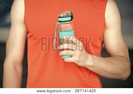 Hand Holds Sportive Bottle Of Water Or Sport Drink, Male Body Background. Bottle Of Water In Muscula