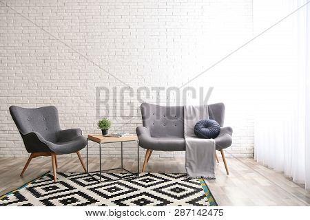Stylish Sofa And Armchair Near Brick Wall In Modern Living Room Interior. Space For Text