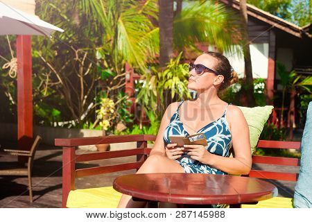 Woman Relaxing Outdoors On A Summer Sunny Day In A Luxury Hotel On The Coast Of The Resort Of Ngapal