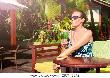 Attractive Woman Enjoying A Tropical Cocktail On Vacation On A Background Of Luxurious Bungalows.