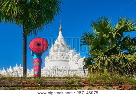 Young Woman In Traditional Dress With An Umbrella Is Looking At The Hsinbyume-paya Pagoda Near The O