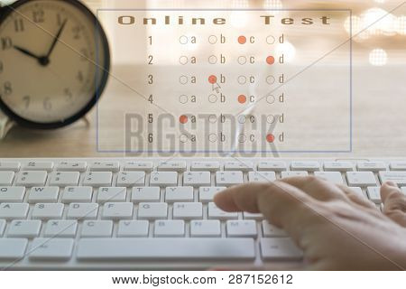 Dry Hand Of Adult Student Is Using Mouse And White Keyboard On Wood Table To Do Test Examination Wit