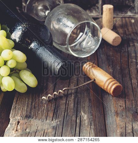 Bottle Of Red Wine With Fresh Grape And Bunch Of Corks On Wooden Table